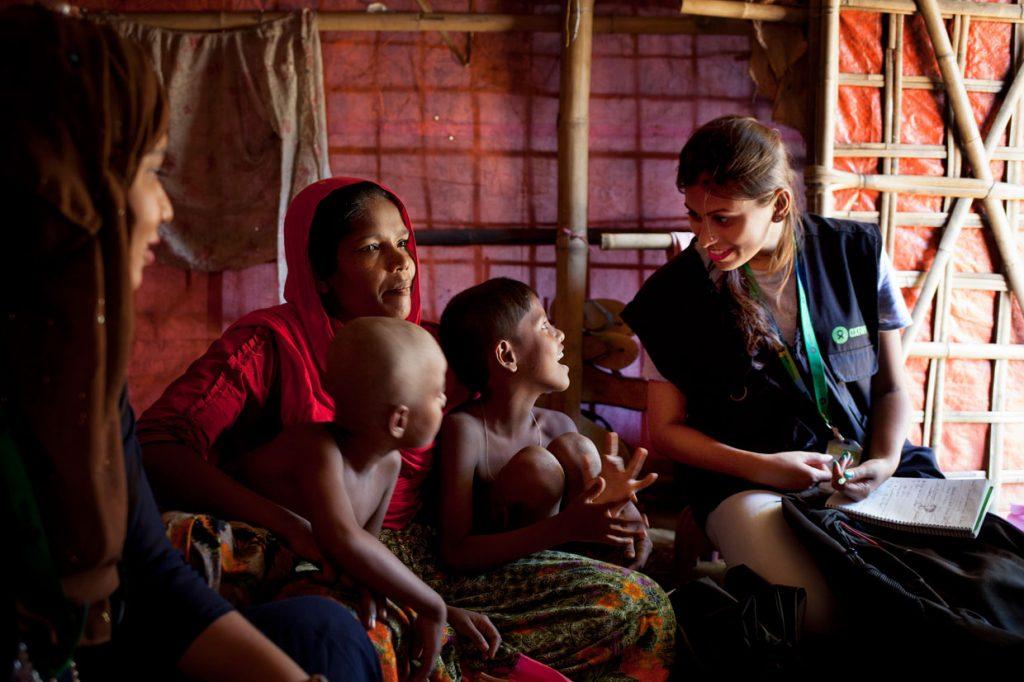 Iffat conversa com locais durante suas visitas como voluntária da Oxfam.